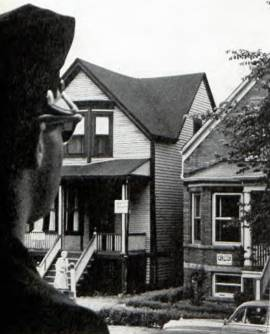 Chicago policeman guards the first black-owned home on a formerly all-white block. Note FOR SALE signs across street.